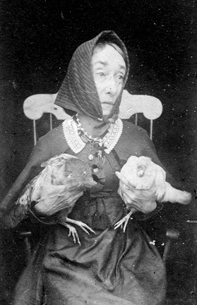 Nancy Luce holding two chickens, photo in the public domain