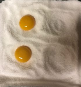 egg yolks placed in salt-sugar mixture for curing
