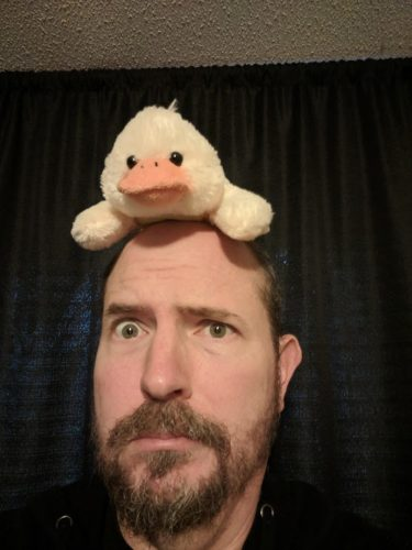 Man with toy duck on his head
